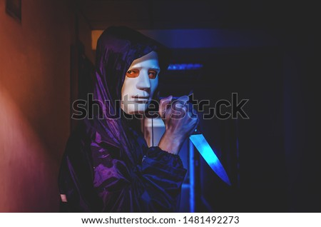murder, kill and people concept - Criminal or murderer in black wearing a white mask holding knife inside a condo at crime scene Сток-фото ©