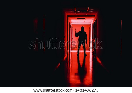 murder, kill and people concept - Criminal or murderer wearing a mask in silhouette holding knife inside a condo at crime scene Сток-фото ©