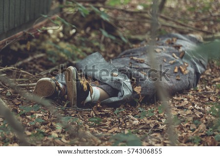 Murder victim wrapped in tarpaulin with feet protruding in leafy forest Сток-фото ©