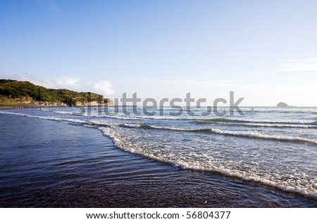 Muriwai Beach on a bright sunny evening with people playing in the surf
