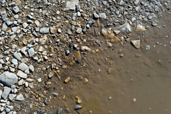 Murky dirty water from a muddy puddle recedes from the edge of stone pebbles as it evaporates due to the heat