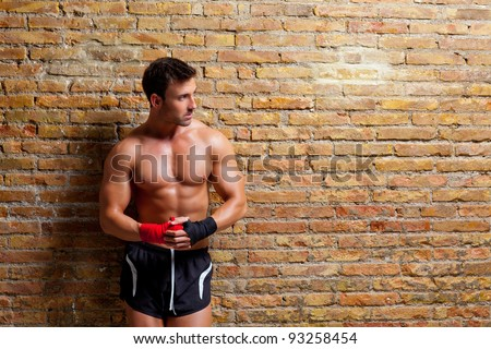 muscle boxer shaped man with fist bandage in red and black on brick wall