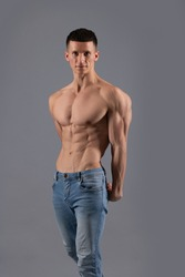 Muscle fitness. Fit man pose shirtless grey background. Bodybuilder with muscular torso. Six pack abs training. Physical fitness and sport. Bodybuilding. Developing musculature.
