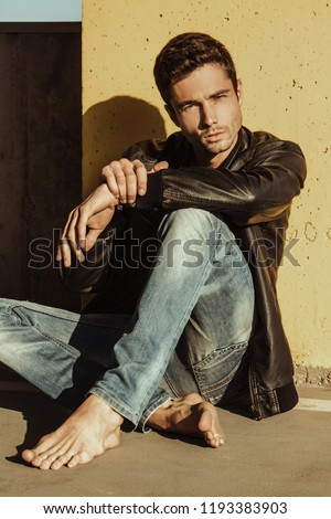 Muscle handsome stripped male model in denim blue jeans and black leather jacket on urban parking background