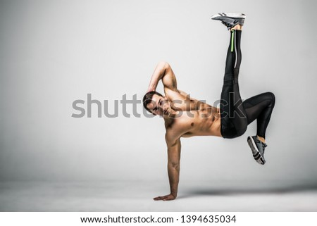 Muscle male model in black treand sportswear in a jumping pose on gray background. Studio shoot.