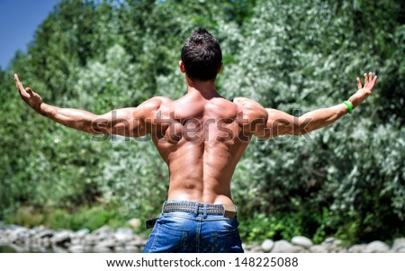 Muscle man in jeans, outdoor with arms spread open, seen from the back, muscular shoulders