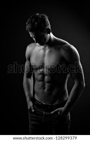 Muscle sexy naked young man with perfect body posing in jeans