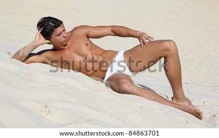 Muscle sexy wet naked young man lying on the sands