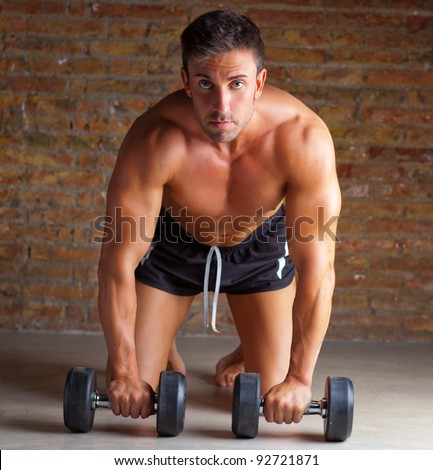 muscle shaped man on knees with training weights on brick wall