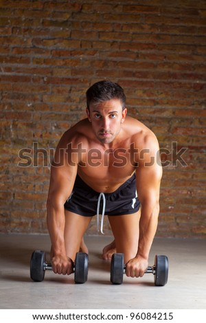 muscle shaped man on knees with training weights on brickwall