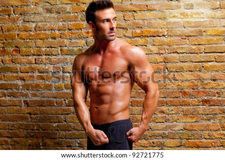 muscle shaped man posing on gym grunge brick wall