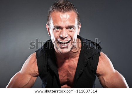 Muscled fitness man. Cool looking. Tough guy. Blue eyes. Blond short hair. Wearing black shirt. Tanned skin. Studio shot isolated on grey background.