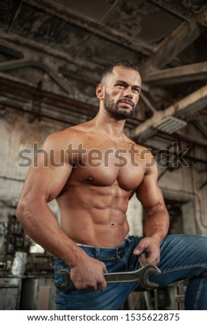Muscled half naked man at work in an old factory.