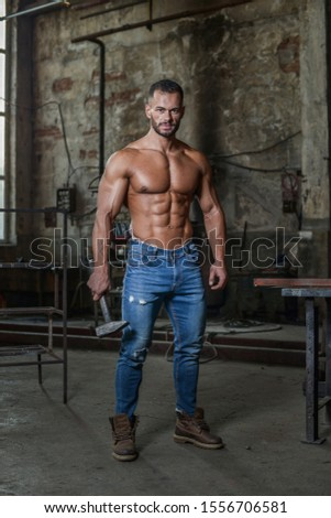 Muscled half naked man at work walking in an old factory.