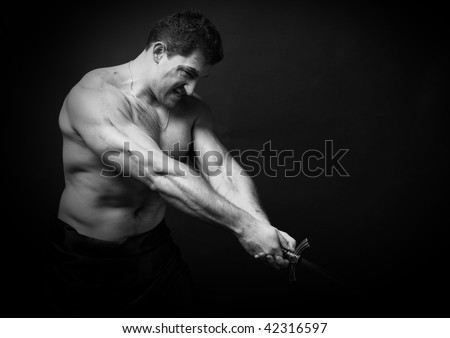 Muscled male model in studio with a sword
