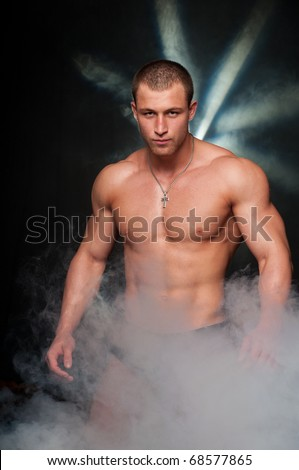 Muscled male model posing in studio with a smoke