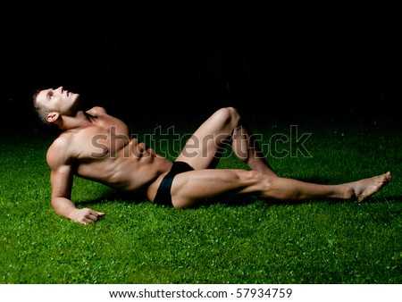 Muscled male model posing on the grass
