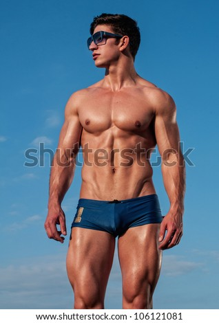 Muscled male model with a sky background - stock photo