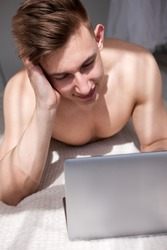 Muscled man have online chatting with girl on bed. Sunny romantic morning at home.