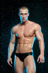 Muscled man posing in studio with water drops