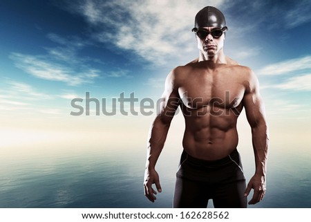 Muscled swimmer man with cap and glasses outdoor at a lake with blue cloudy sky. Extreme fitness sport.