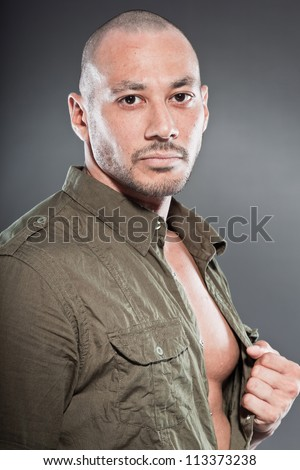 Muscled tough guy wearing green army shirt. Good looking man. Isolated on grey background. Studio shot. Healthy. Fitness.