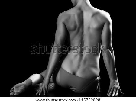 Muscled woman sitting on black floor