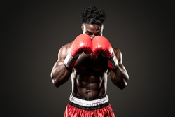 Muscular African American Black male sweaty boxer covers his head as he comes  towards the camera  with dramatic lighting with a black background
