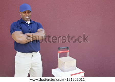 Muscular African American man standing with arms crossed and hand truck over colored background stock photo