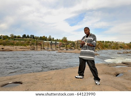 Muscular African american man wearing chains standing on the rocks of a river.