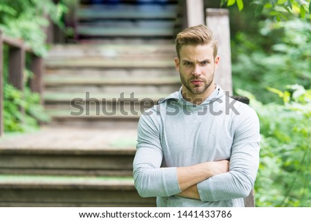 Muscular and confident. Muscular man on summer day. Athletic guy keeping muscular arms crossed at park stairs. Handsome sportsman or athlete showing muscular strength and power.