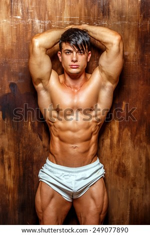 Muscular and good shaped young bodybuilder poses over the wall