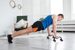 Muscular and Strong Athletic Fit Man in T-shirt and Shorts is Doing Push Up Exercises at Home in His Spacious, Sunny and Light Living Room with Modern Interior.