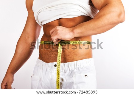 Muscular and tanned man is being measured