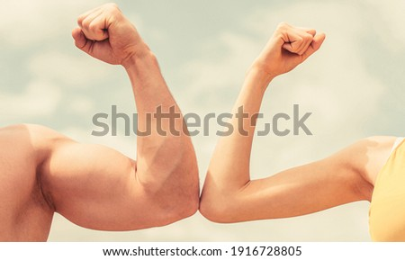 Muscular arm vs weak hand. Vs, fight hard. Competition, strength comparison. Rivalry concept. Hand, man arm fist Close-up. Rivalry, vs, challenge, strength comparison. Sporty man and woman.