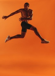 Muscular athlete twisting waist while jumping in air. Bare chested fit man doing fitness workout on orange background.