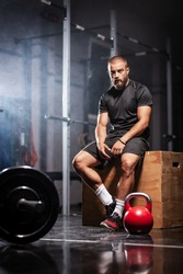 Muscular athlete with weightlifting equipment. Trainer in a fitness studio. Smoke background.