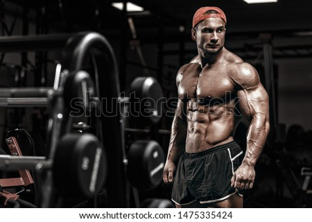 Muscular athletic bodybuilder sport man posing after exercises over dramatic light in gym and looking raised eyebrow outside