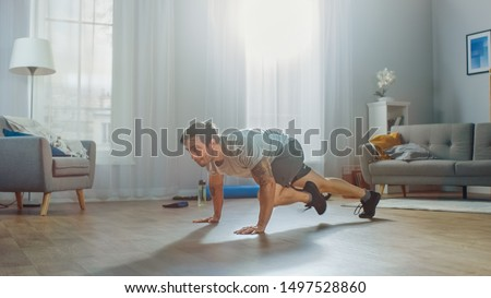 Muscular Athletic Fit Man in T-shirt and Shorts Energetically Starts Doing Mountain Climber Exercises at Home in His Spacious and Bright Apartment with Modern Interior.