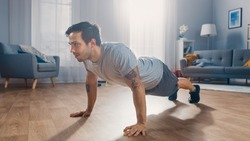 Muscular Athletic Fit Man in T-shirt and Shorts is Doing Push Up Exercises at Home in His Spacious and Bright Apartment with Minimalistic Interior.