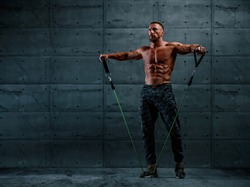 Muscular Athletic Men Exercise With Resistance Band. Copy Space