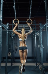 Muscular back of a girl Crossfit athlete in black sportswear is hanging on gymnastic rings with his back to the camera. Work out in the gym. Caucasian woman with long blond hair training olympic ring.