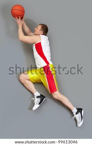 Muscular basketball player slamming the ball, overview