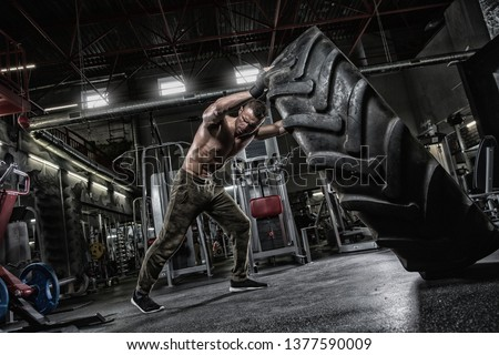 Muscular bearded tattooed fitness shirtless man moving large tire in street gym. Concept lifting, workout training