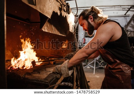 Muscular blacksmith splits metal in the furnace for processing iron on the anvil