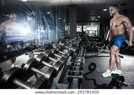 Muscular bodybuilder guy doing exercises with dumbbell in gym