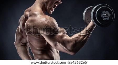 Muscular bodybuilder guy doing exercises with dumbbell over black background