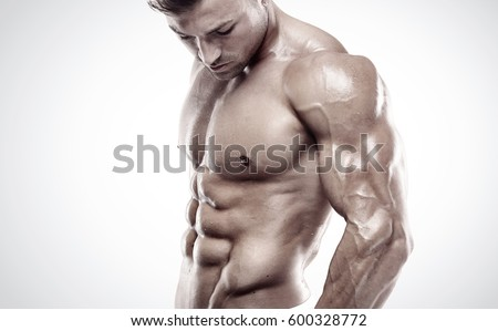 Muscular bodybuilder guy standing and posing triceps muscle