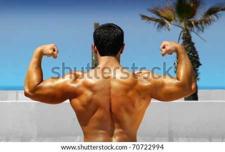 Muscular bodybuilder showing his back on the beach