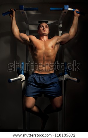 Muscular bodybuilder training in dark background